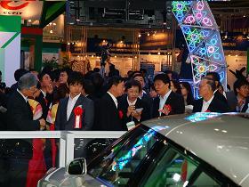 写真。展示会場を視察する新藤副大臣。