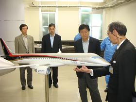写真。MRJについて説明を受ける新藤副大臣