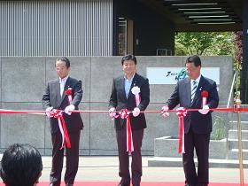 写真。開館のテープカットを行う新藤副大臣。