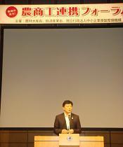 写真。主催者として挨拶を行う新藤副大臣。