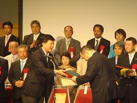 写真。認定証を授与する新藤副大臣。