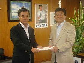 写真。要請書を受け取る新藤副大臣。